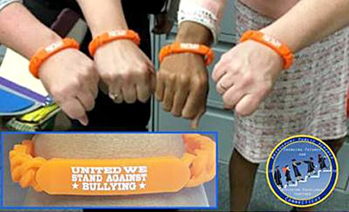 "Staff members wearing orange wrist bands ""United We Stand Against Bullying"""